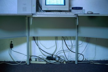 Tangle of cables under computer desk